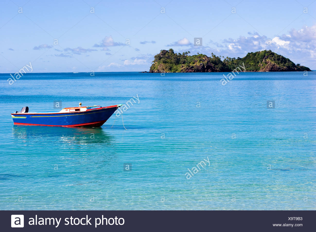 A blue wooden fishing boat floats in the calm waters of Malakati, Fiji. - Stock Image