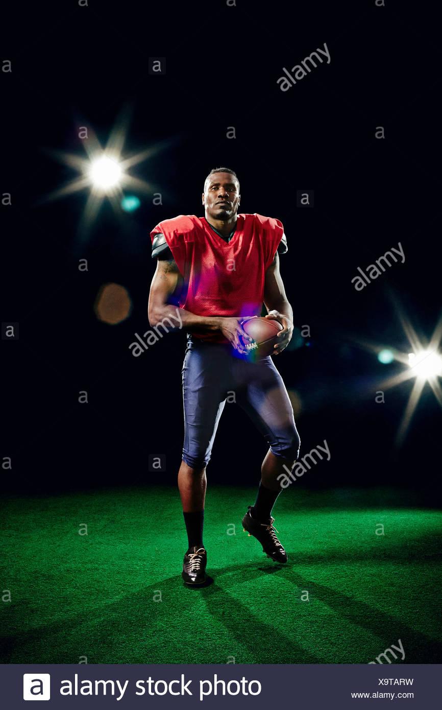 American football player holding ball - Stock Image