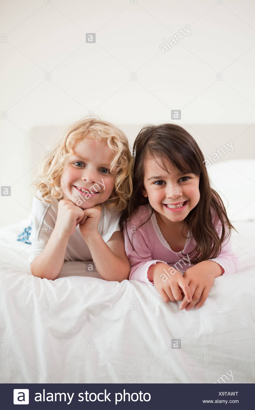 Portrait of children lying on their bellies - Stock Image