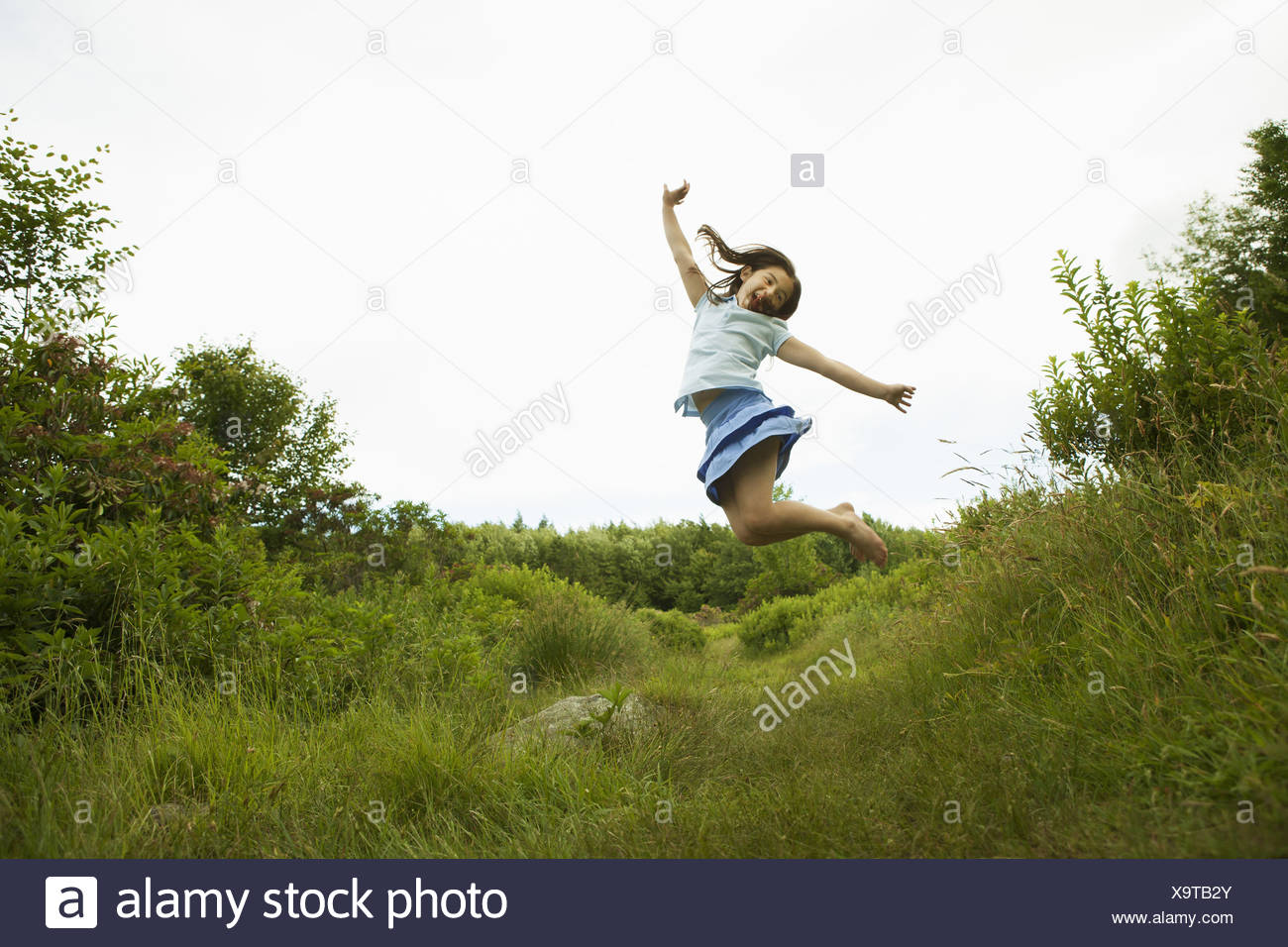 New York state USA young girl leaping for joy kicking up her heels - Stock Image