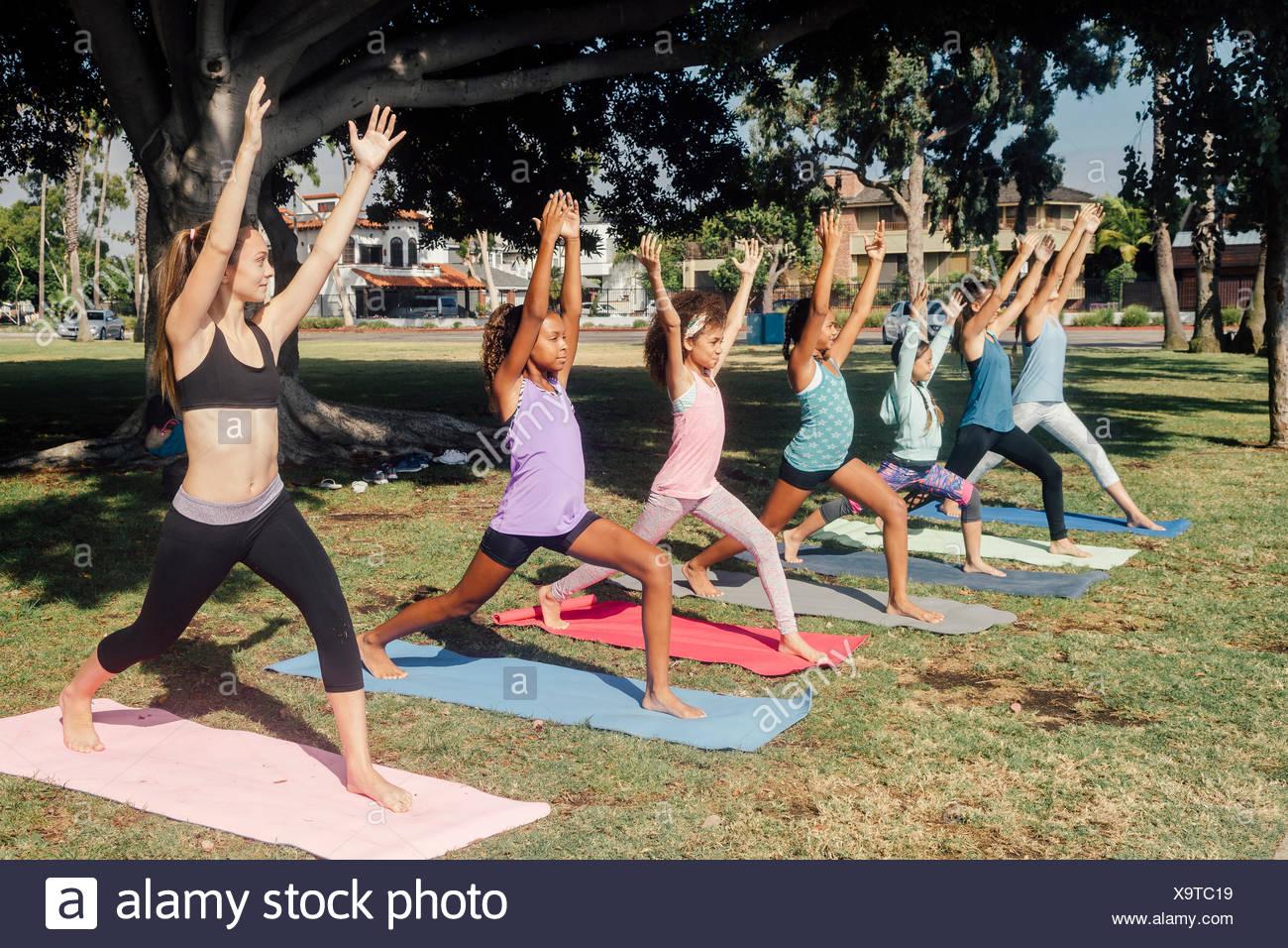 Schoolgirls practicing yoga warrior one pose on school sports field - Stock Image