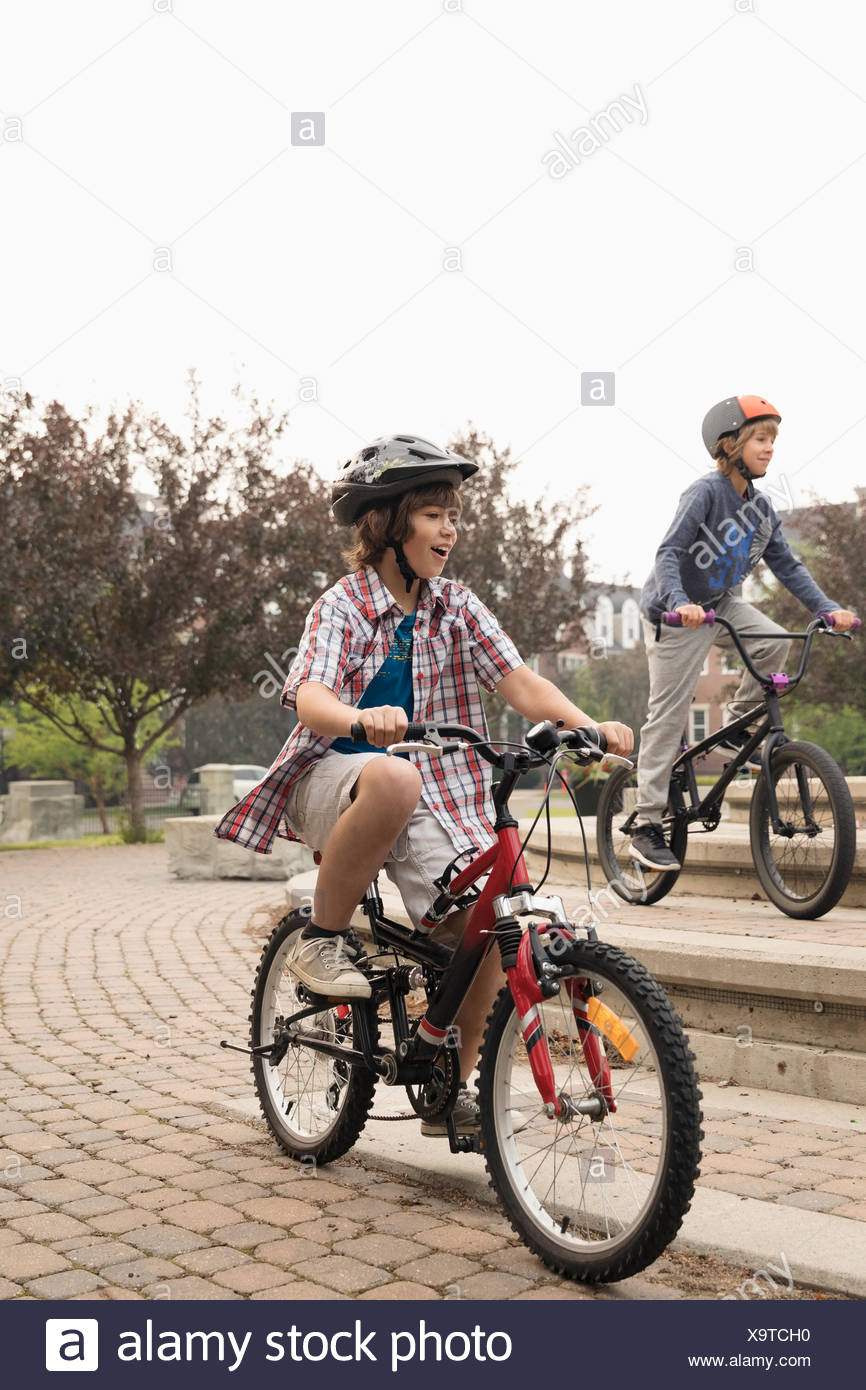 Boy friends riding bicycles in park - Stock Image