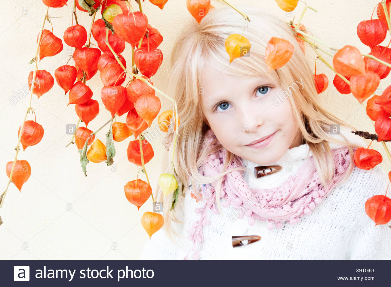 Portrait of smiling girl (6-7) with winter cherries - Stock Image