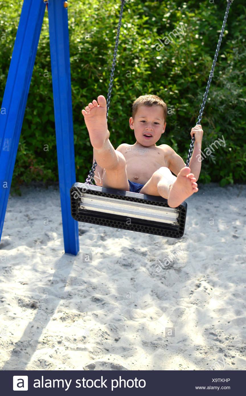 little boy swinging - Stock Image