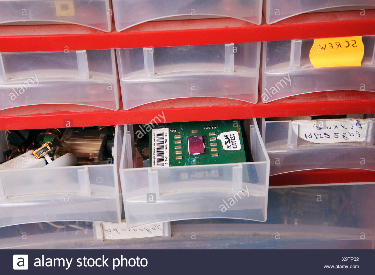 plastic cupboard with spare parts at computer workshop - Stock Image