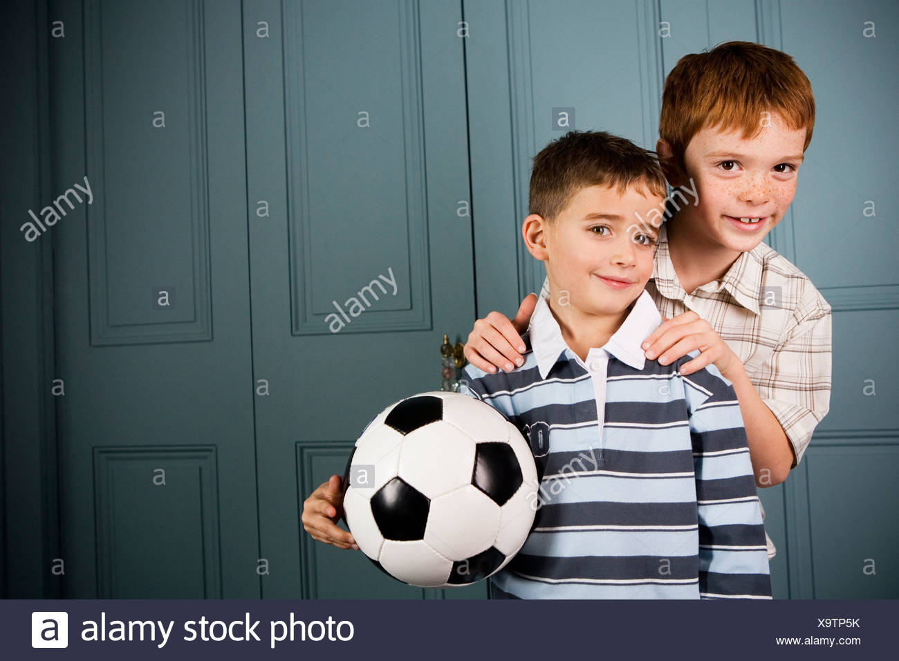 older boy standing behind younger boy hands on shoulders - Stock Image