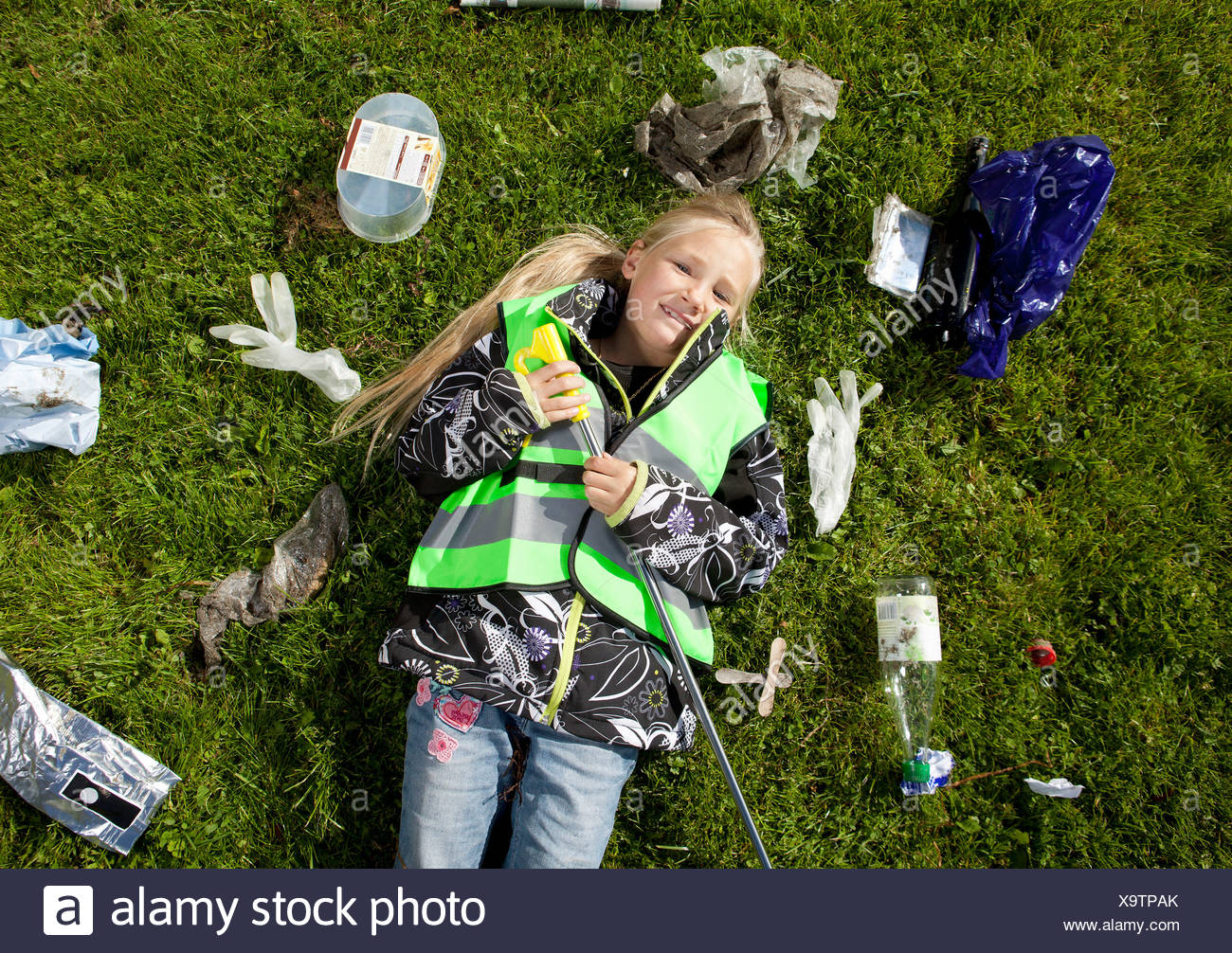 Girl laying in garbage on lawn - Stock Image