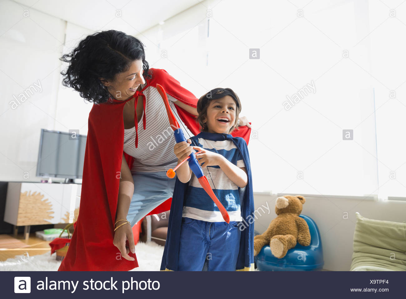 Mother and son in superhero costumes - Stock Image