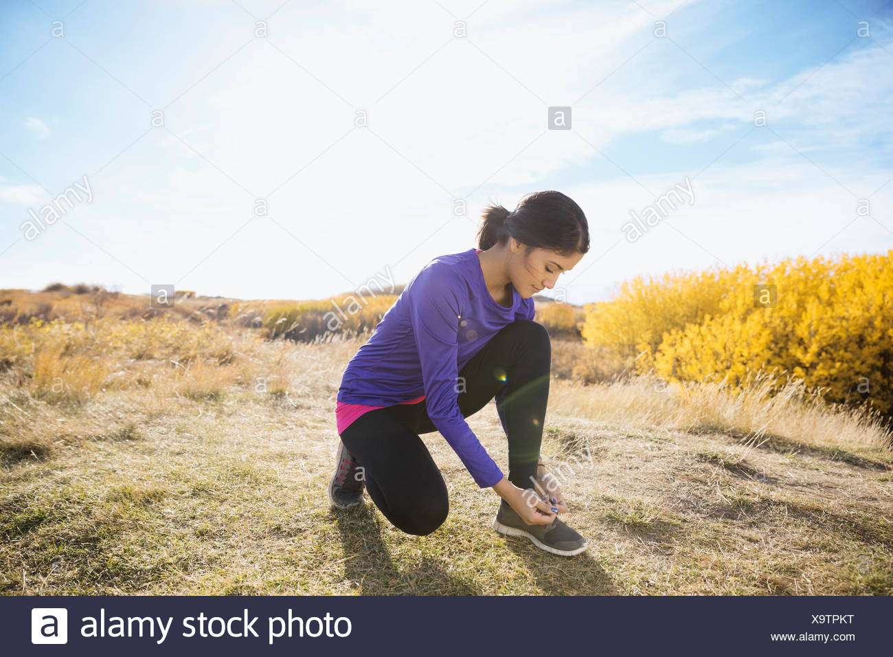 Runner tying shoe in sunny rural field - Stock Image