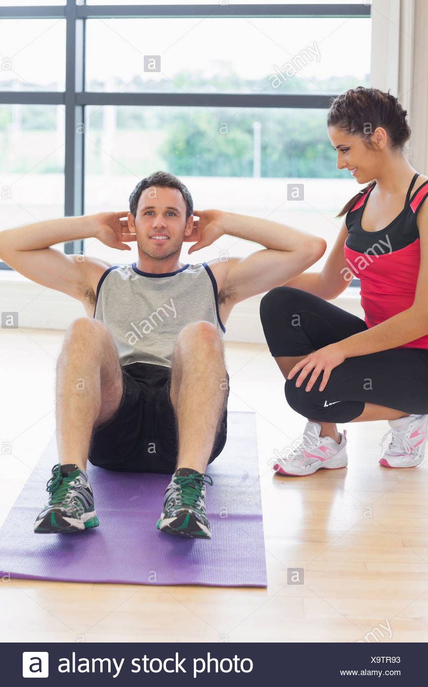 Female trainer watching man do abdominal crunches  on exercise mat - Stock Image