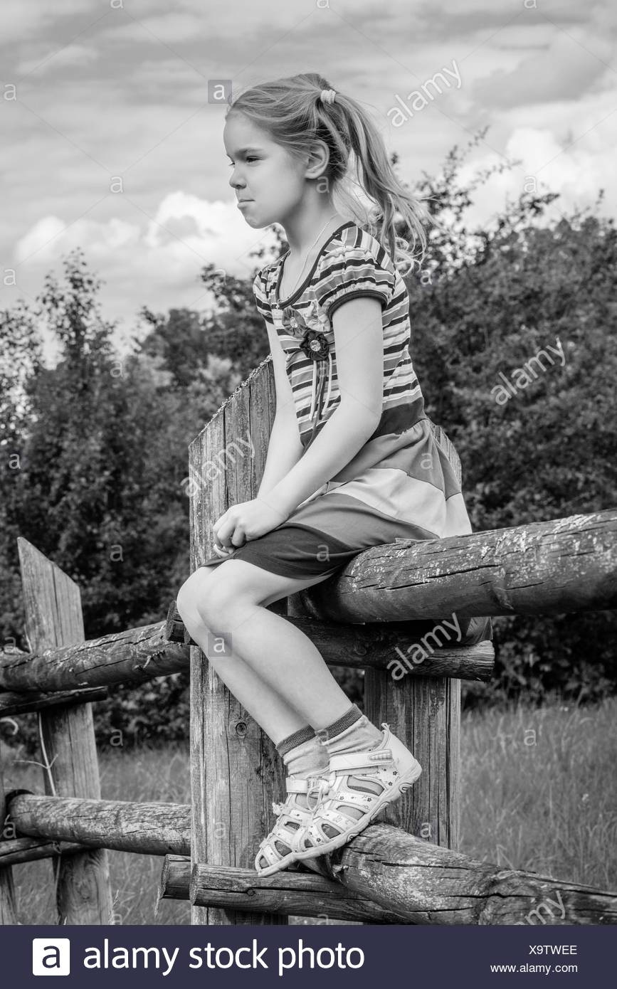 little sad girl sitting on wooden fence - Stock Image