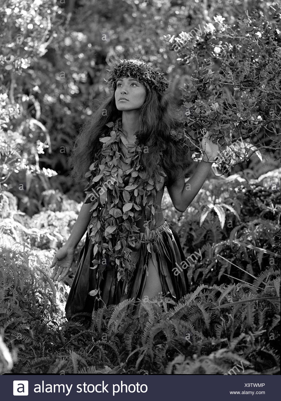 Young Hawaiian girl  near 'Steam Vents' in Hawaii Volcanoes National Park, wearing maile lei and lei poo (head lei). - Stock Image