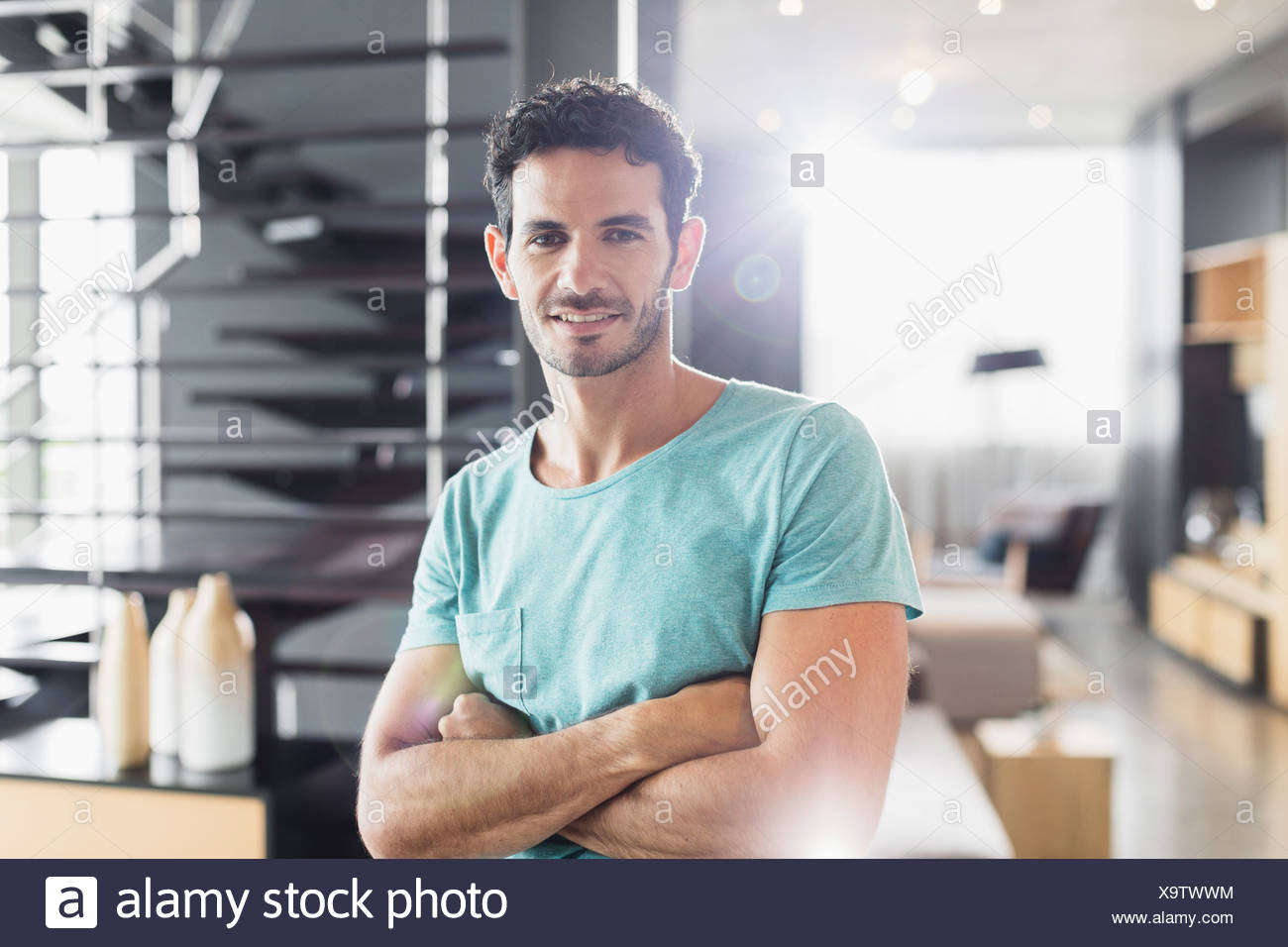 Portrait of smiling man with arms crossed - Stock Image