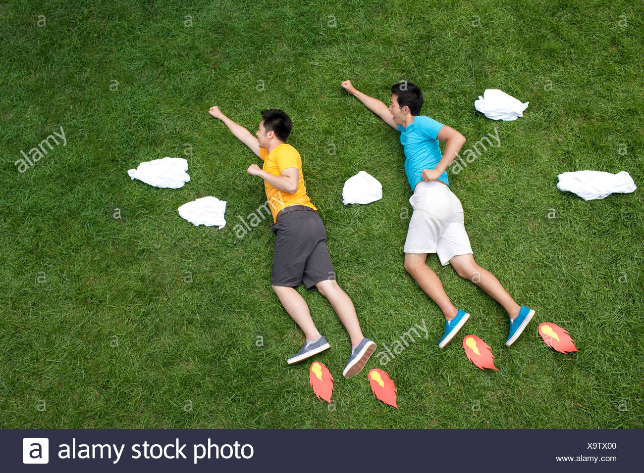 Creative young man imitating flying on meadow - Stock Image