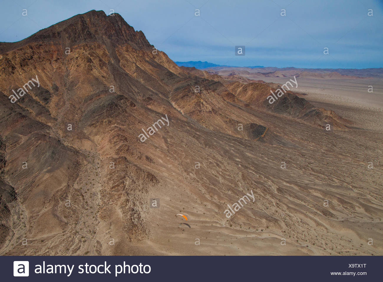 Flying a motorized paraglider over the Mojave Desert near Dumont Dunes, California. - Stock Image