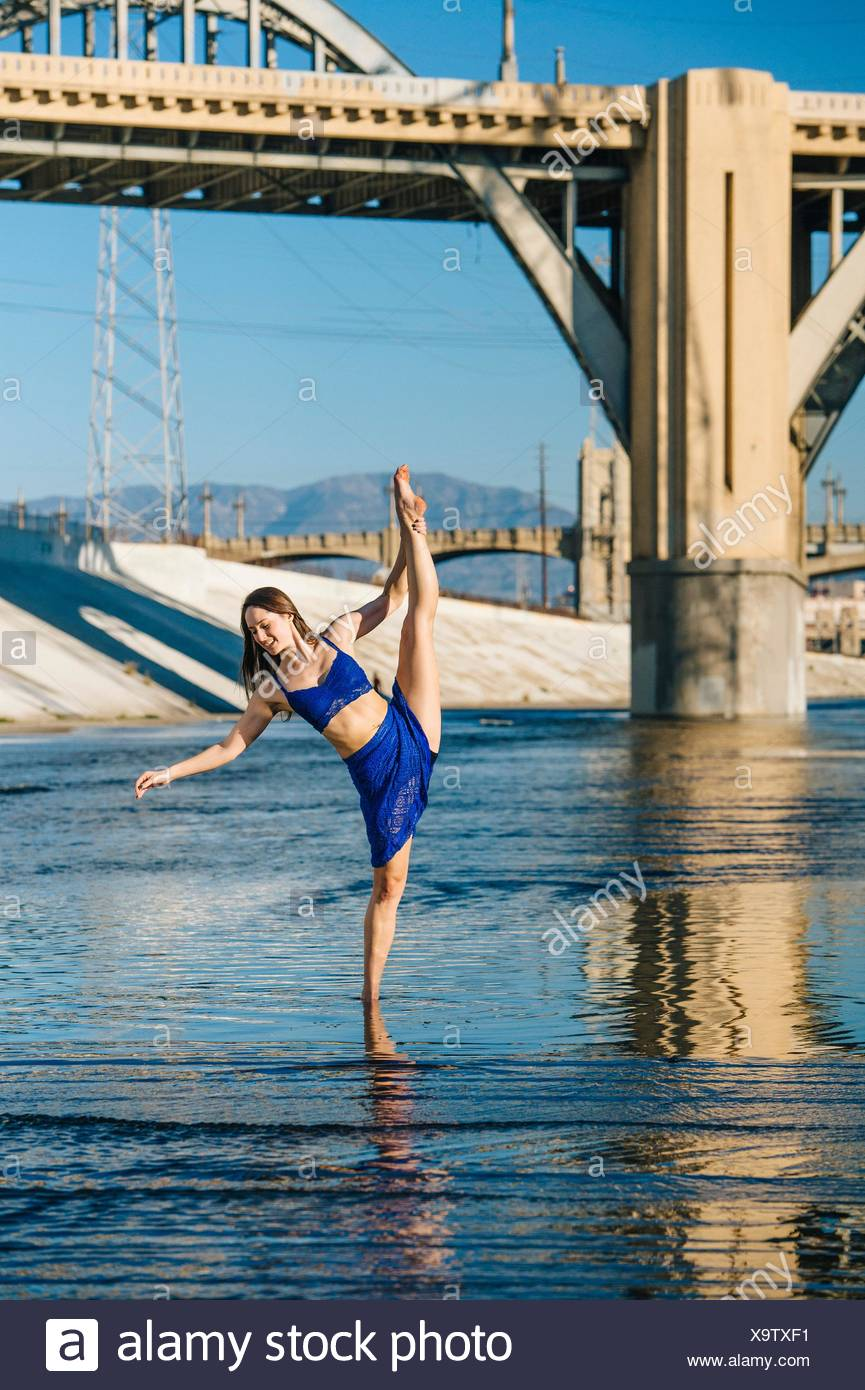 Dancer ankle deep in water, leg raised, balancing on one leg, in front of bridge, Los Angeles, California, USA - Stock Image