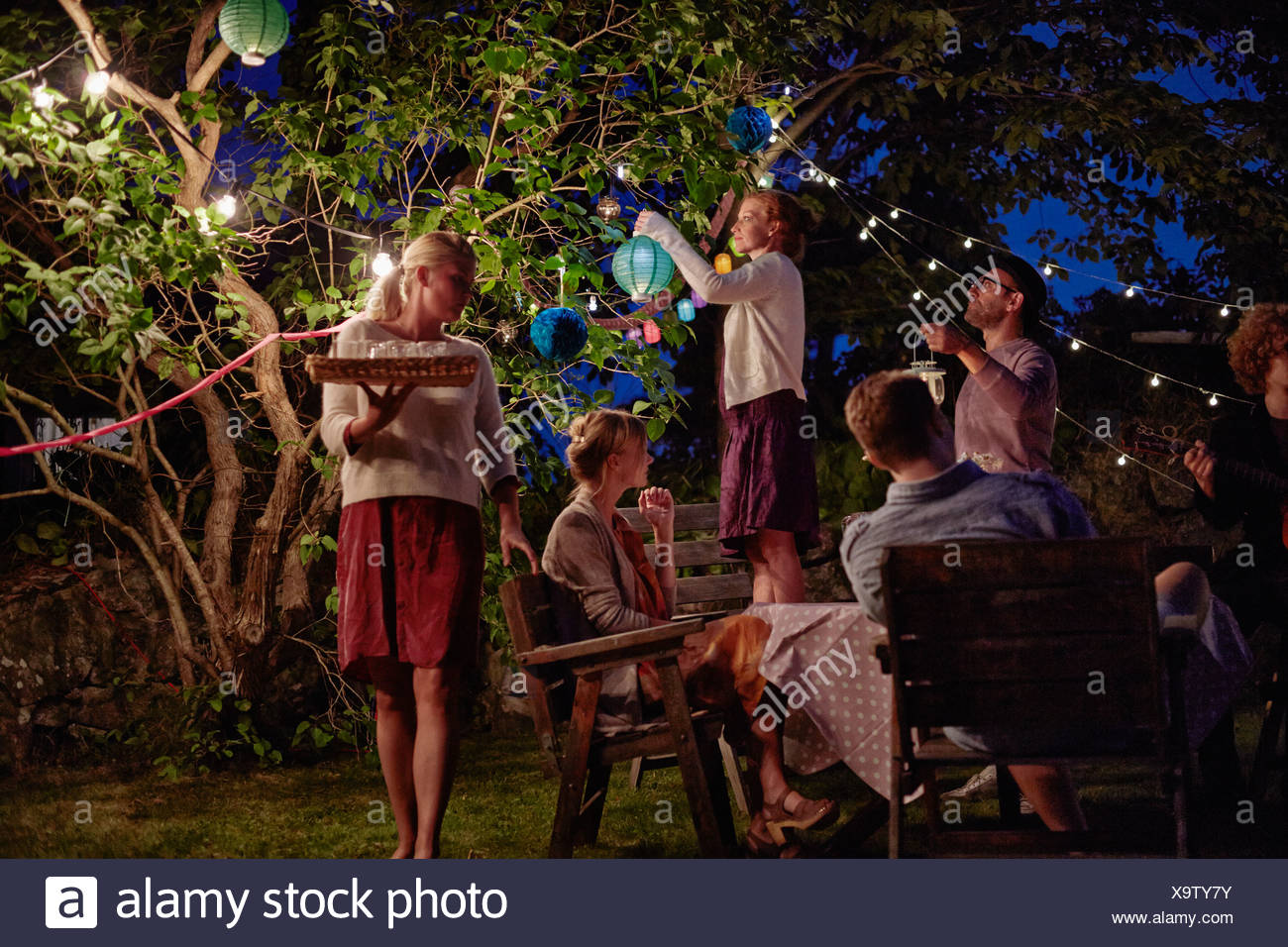 Group of adults preparing for garden party at night - Stock Image