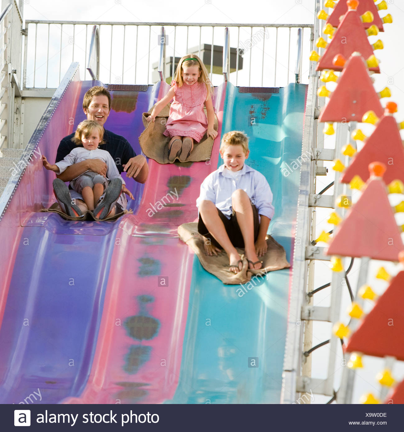 family at the carnival riding on the fun slide together - Stock Image