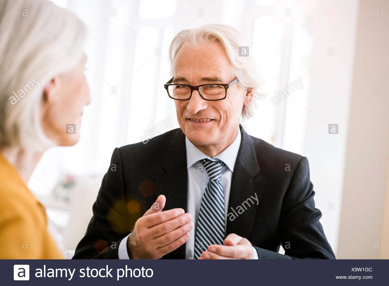 Senior man wearing shirt, tie and suit jacket talking to senior woman - Stock Image