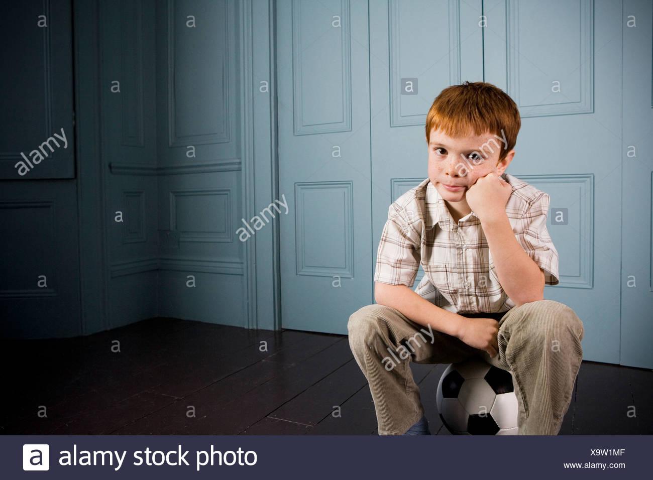 little boy sitting on his football - Stock Image