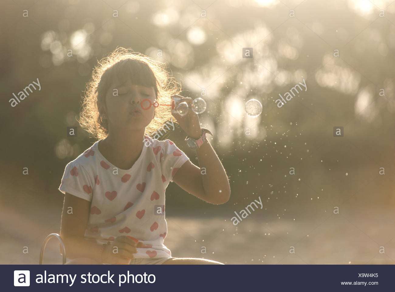Little girl making soap bubbles in the park at twilight - Stock Image