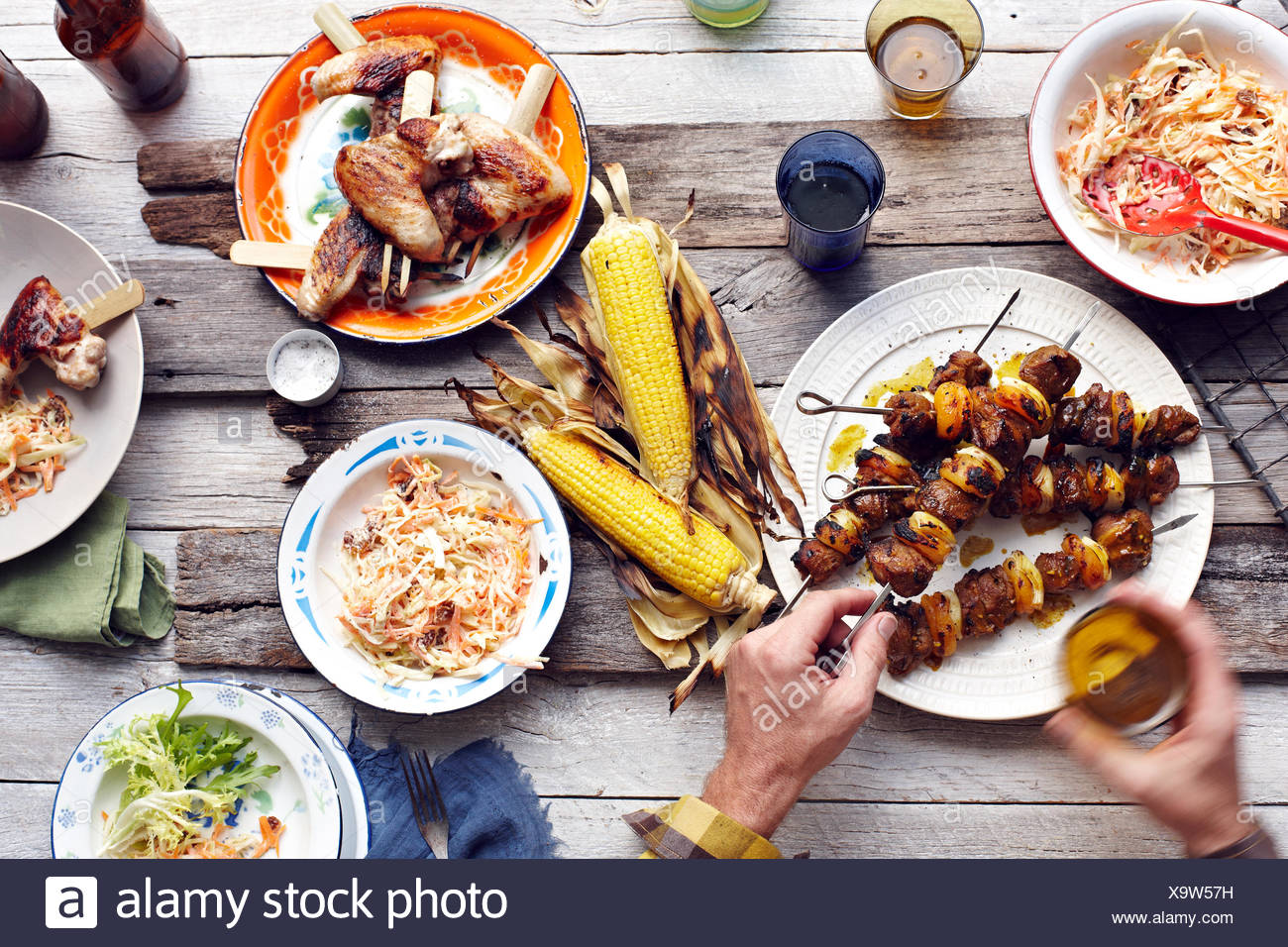 Mans hand picking up lamb and chicken skewer from table - Stock Image