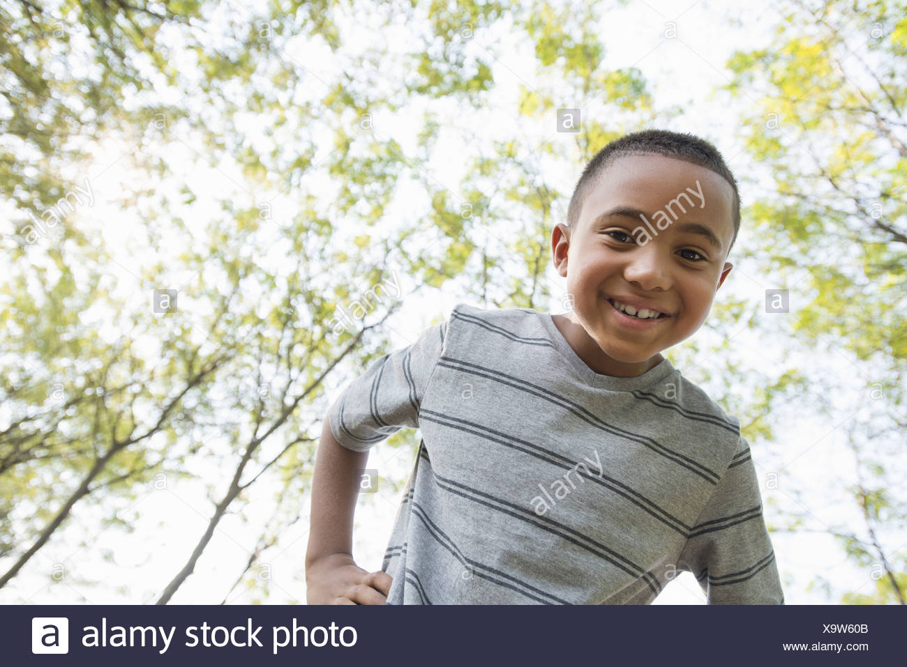 A boy with his hands on his hips looking into  camera. - Stock Image