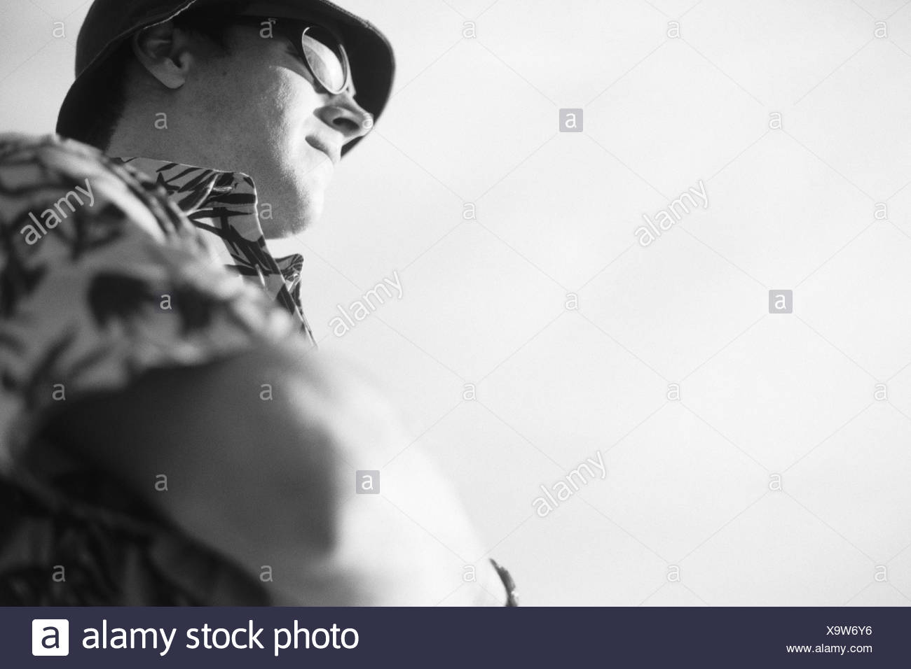 Man, sunglasses, Hawaii shirt, care, arms cross, from below, b/w, vacationers, tourist, think, consider, seriously, thoughts, determination, wait, patience, Ready for of a holiday, view in the distance, steadfastness, outside, Ti3 - Stock Image
