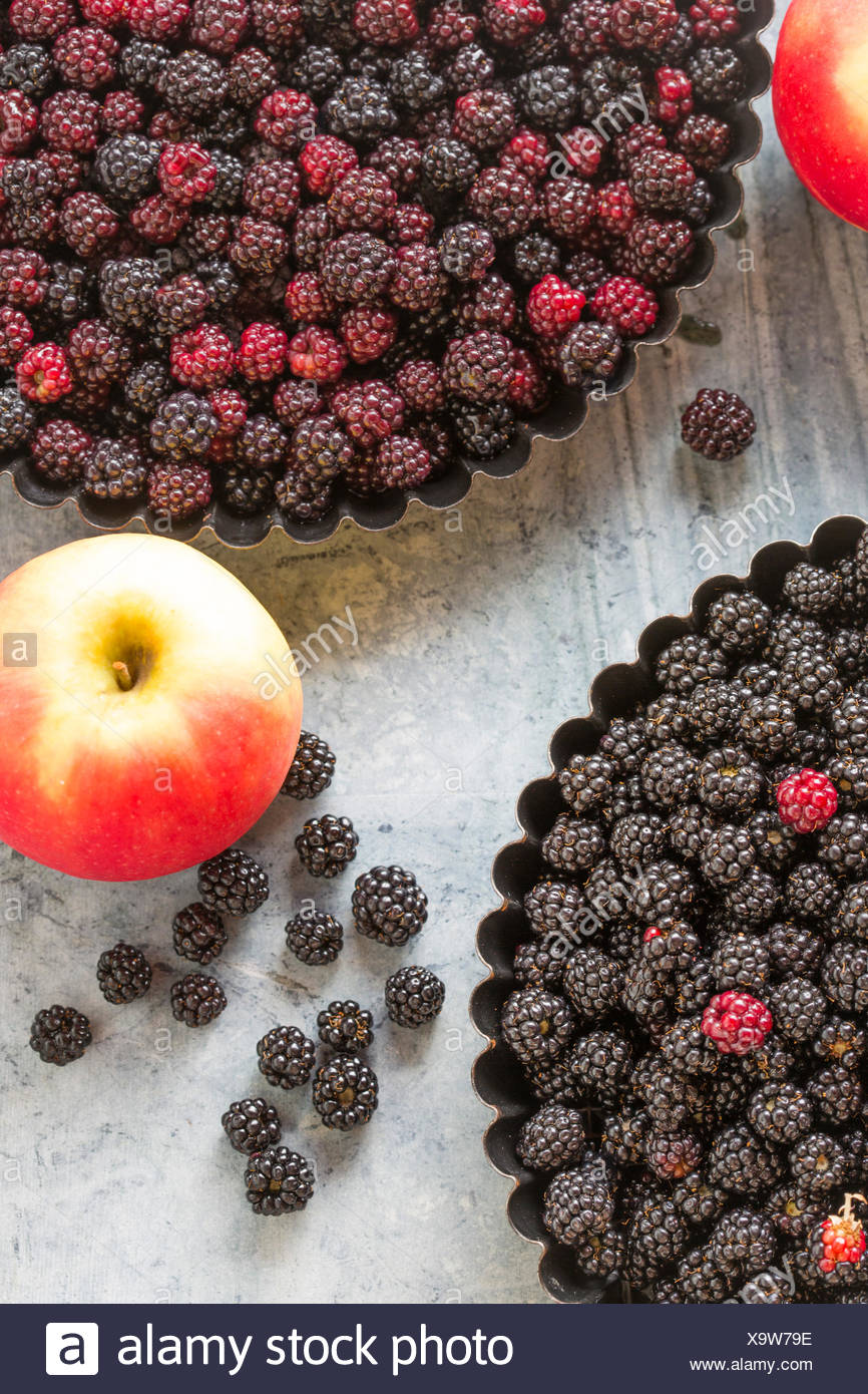 blackberries and rosy apples, for home baking a pie or crumble, agianst green marble, - Stock Image