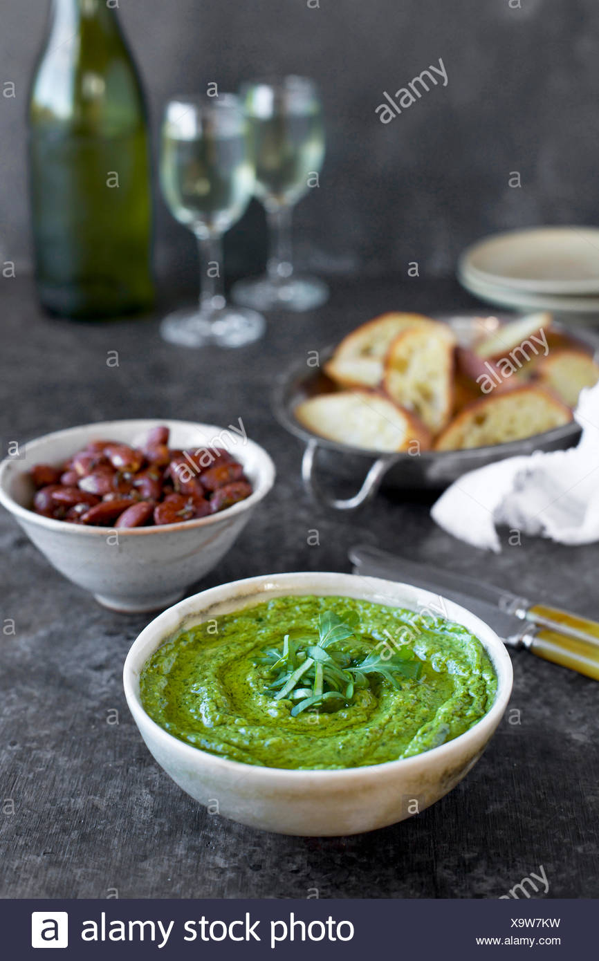 Arugula Chive Basil Pesto served in a ceramic bowl with crostini, almonds and wine.  Photographed fron front view on a black/brown background. - Stock Image