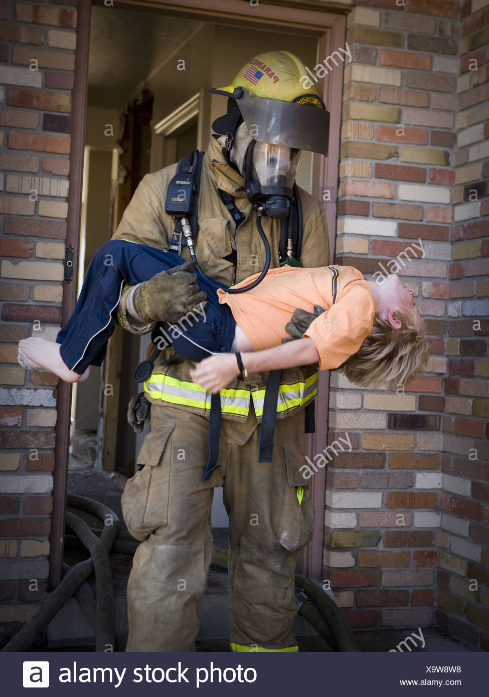 Fire fighter rescuing child - Stock Image