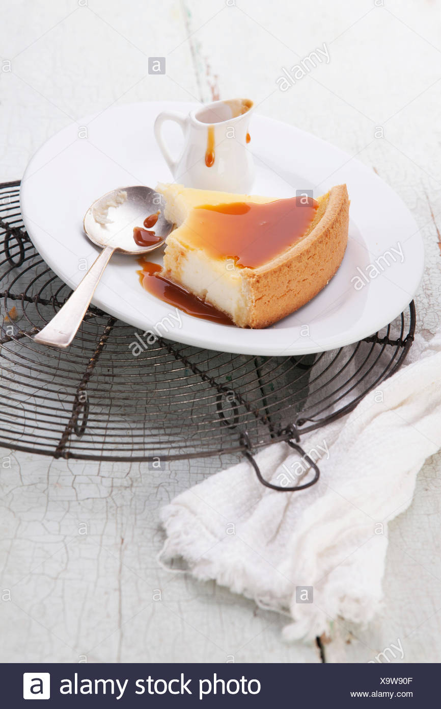 Classical Cheesecake and caramel Sauce on plate on blue texture background - Stock Image