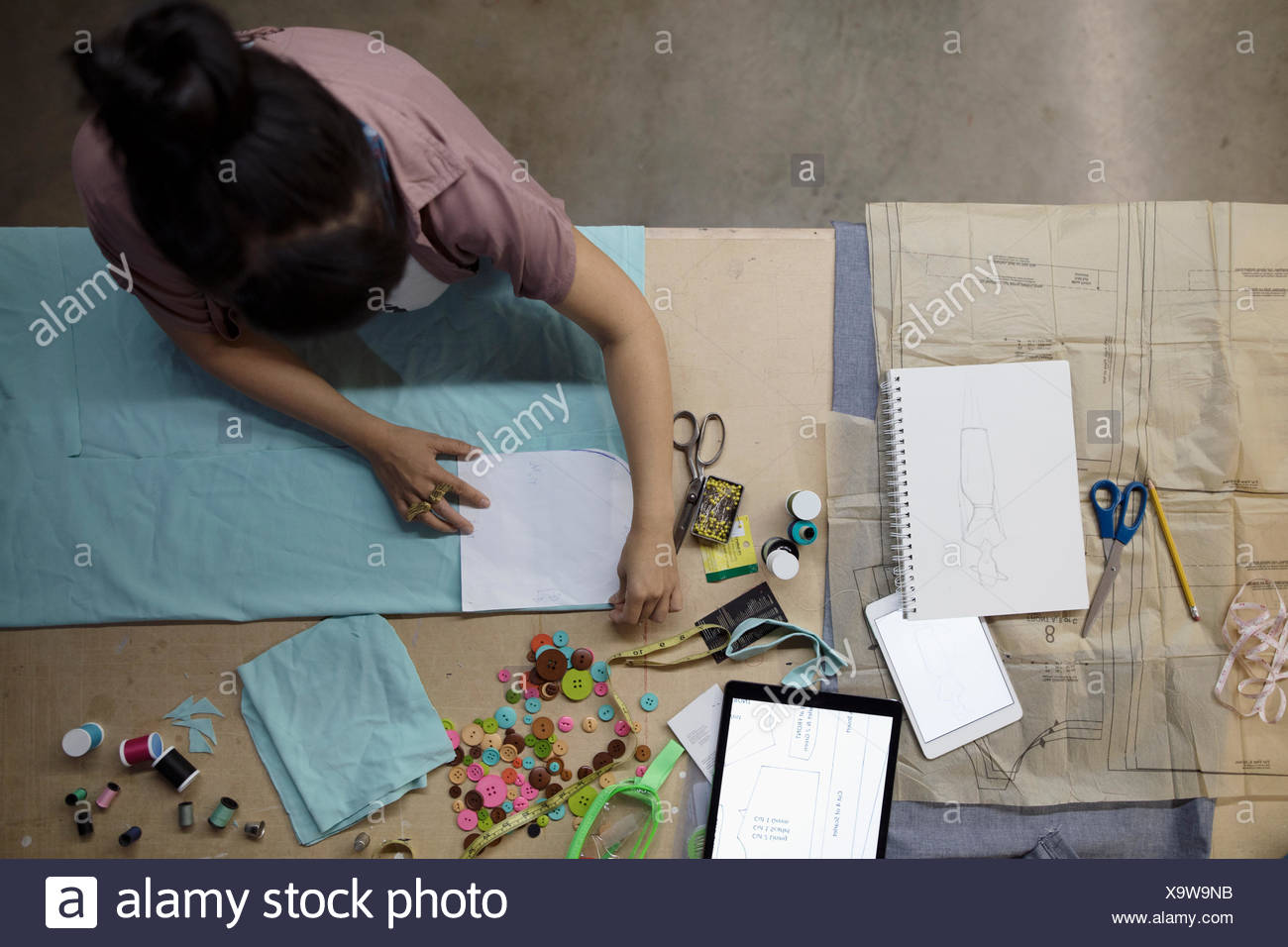Overhead view female fashion designer cutting fabric in workshop Stock Photo