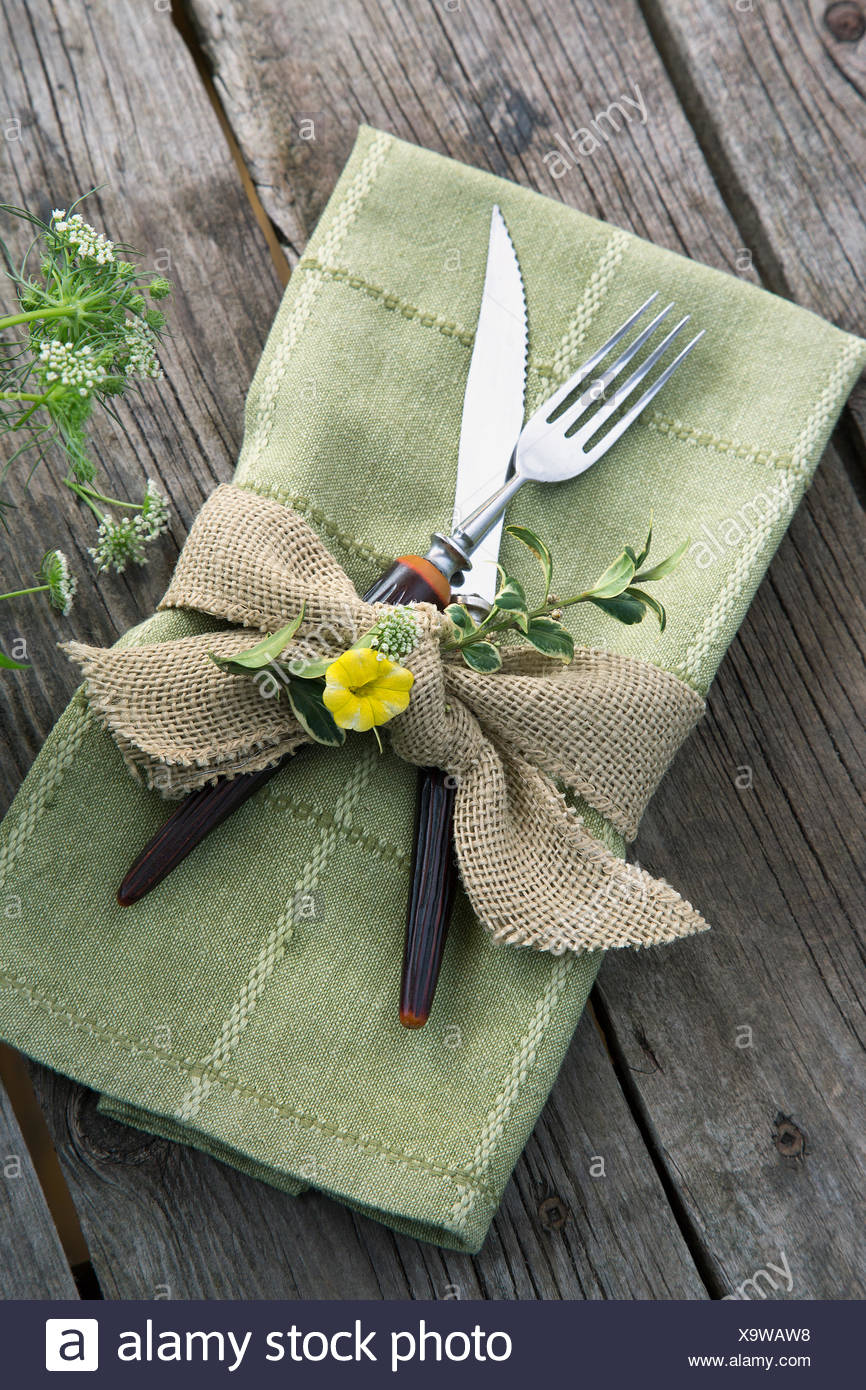 Burlap ribbon and herbs around napkin and silverware - Stock Image