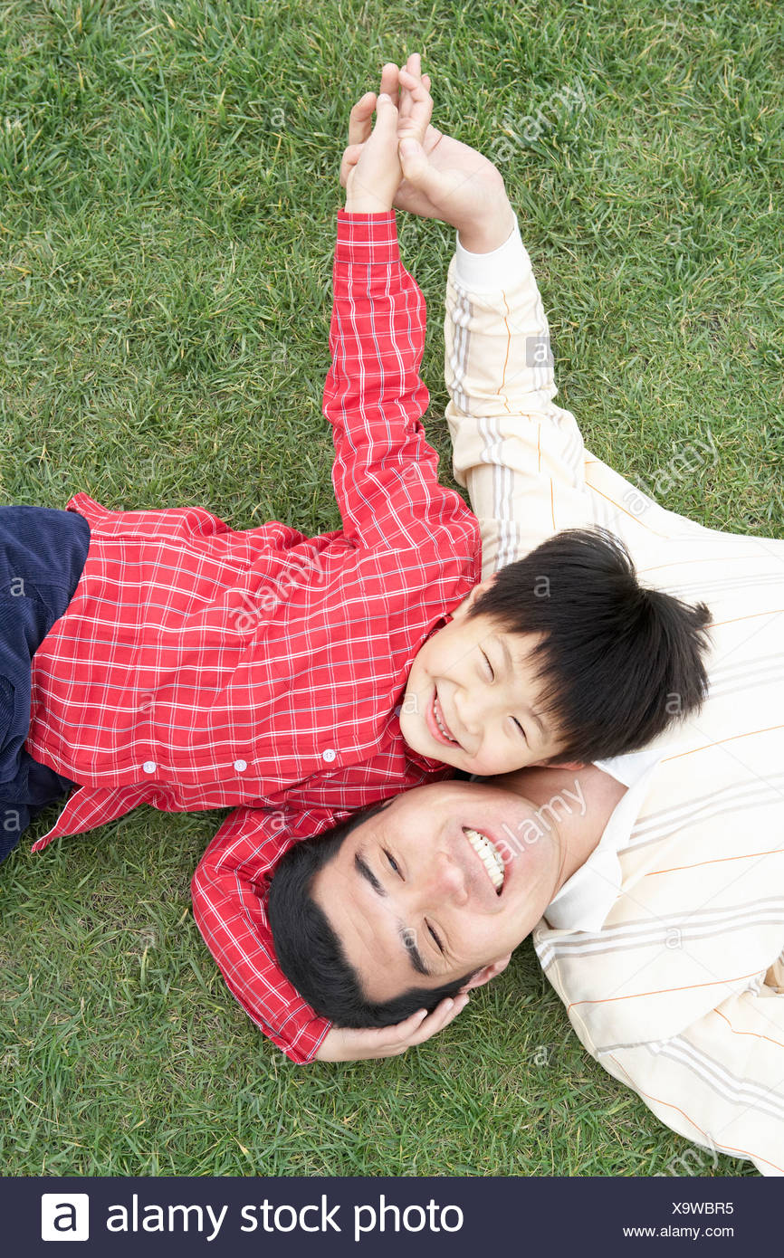 Father And Son Lying Down On Grass Together Stock Photo