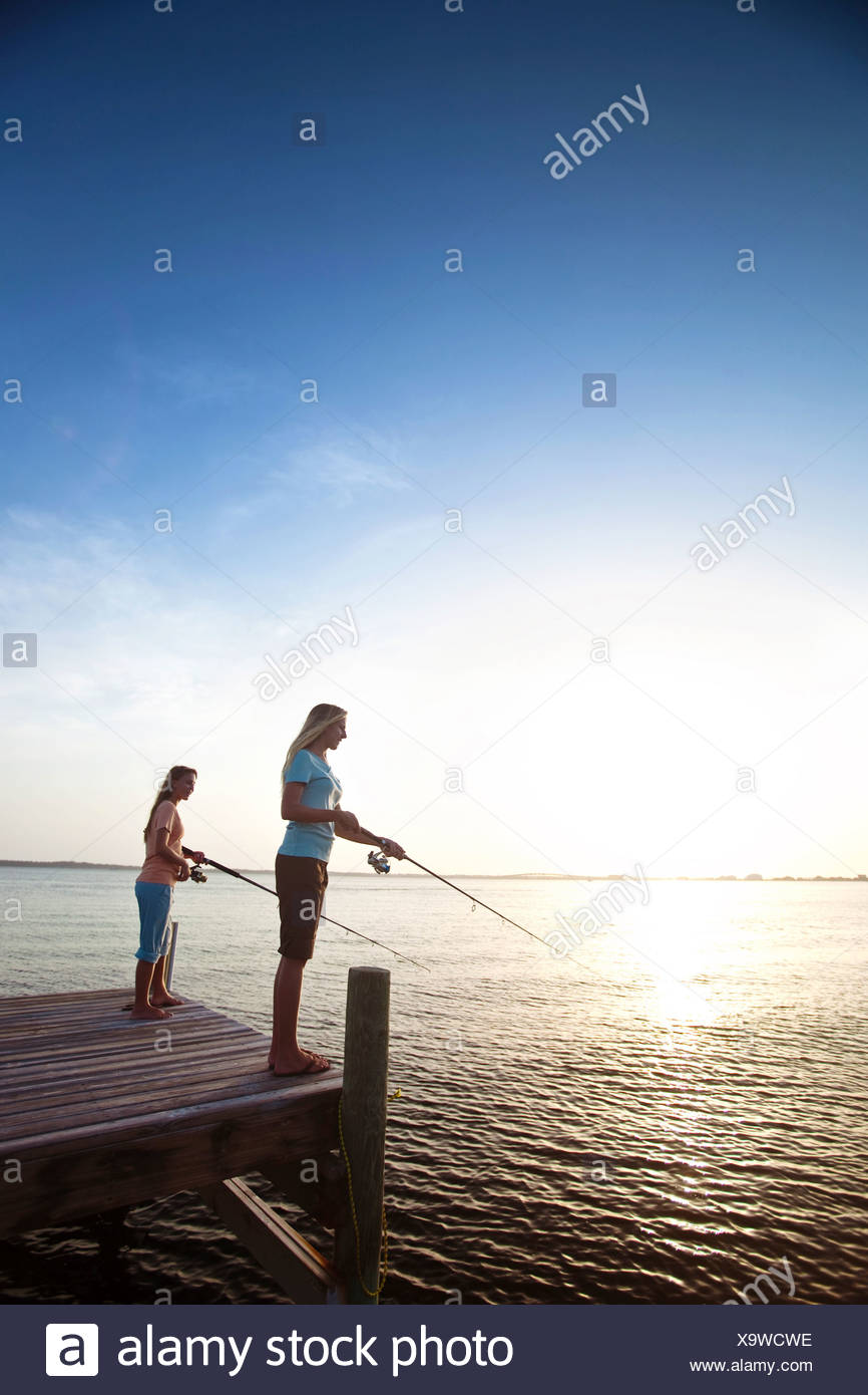 Two girls fish off a pier on the Santa Rosa Sound, Pensacola Beach, Florida at sunset. Stock Photo