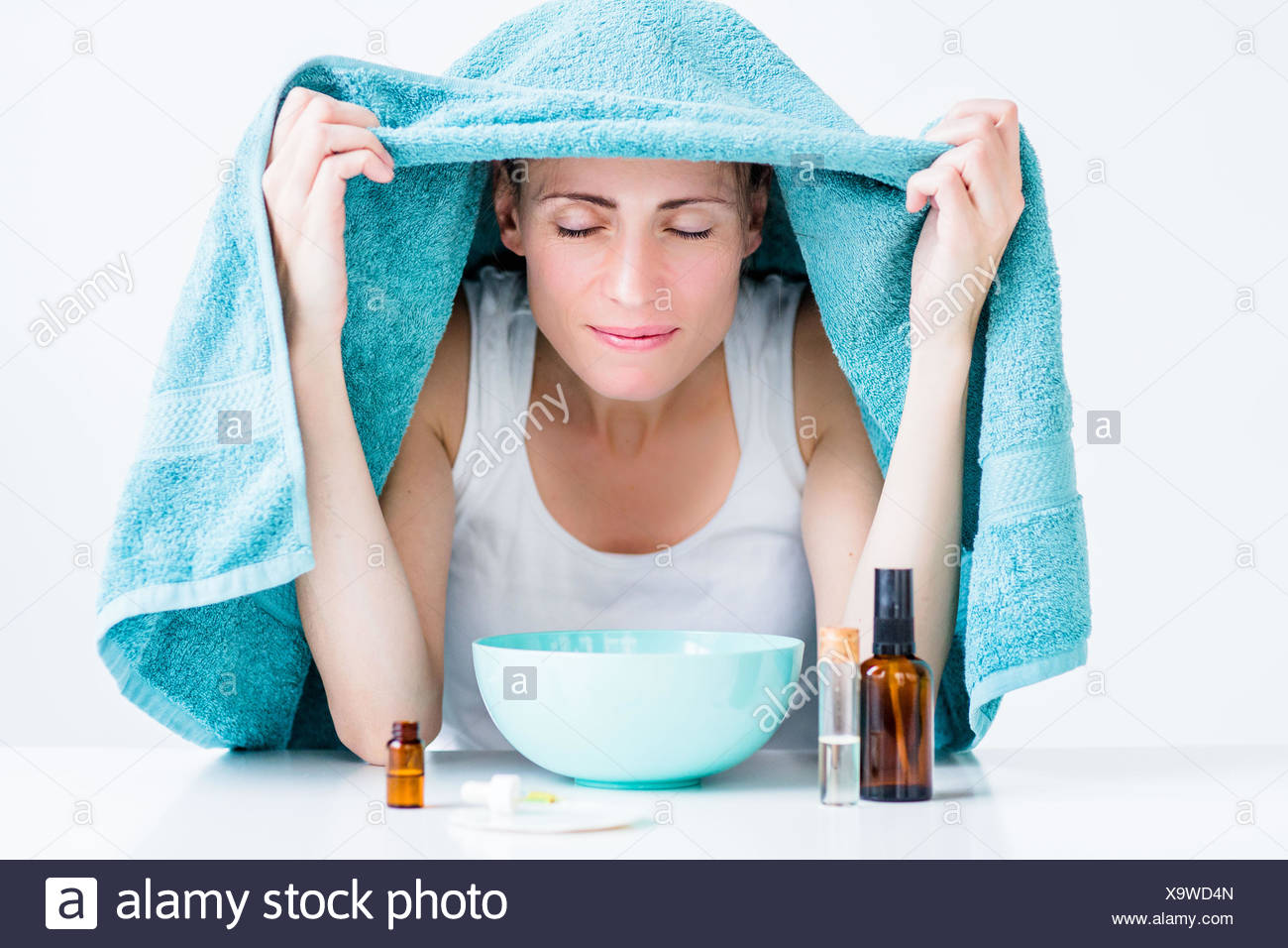 Woman treating a nasal congestion with an inhalation. - Stock Image