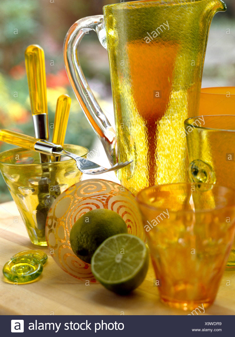 Close-up of a lime green glass jug with orange glasses and a cut lime Stock Photo