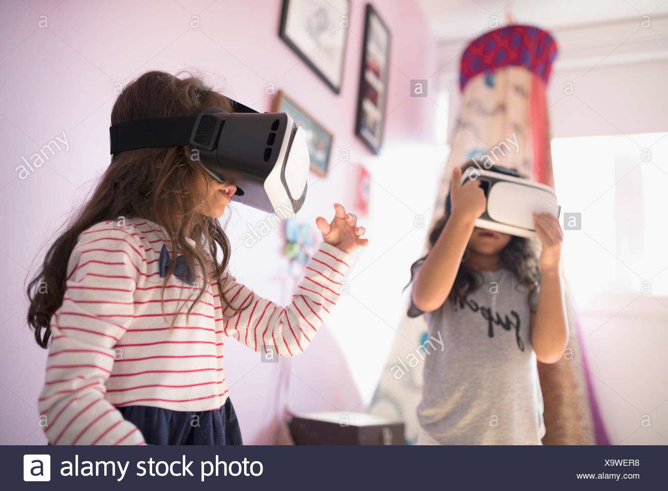 Girl sisters playing with virtual reality simulator glasses in bedroom - Stock Image
