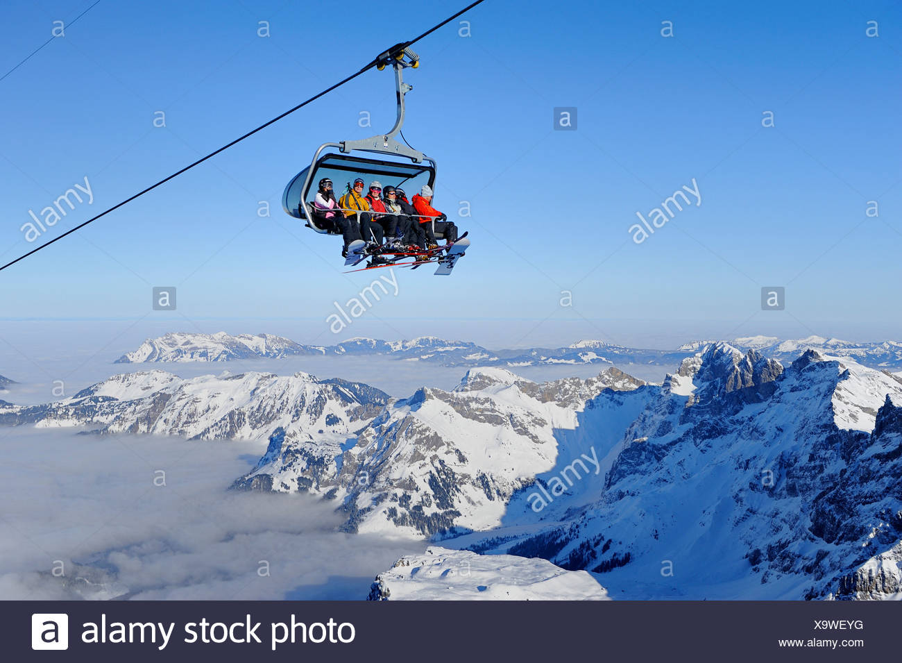 Skiers in a chairlift heading towards Titlis mountain, Engelberg, Obwalden, Switzerland, Europe - Stock Image