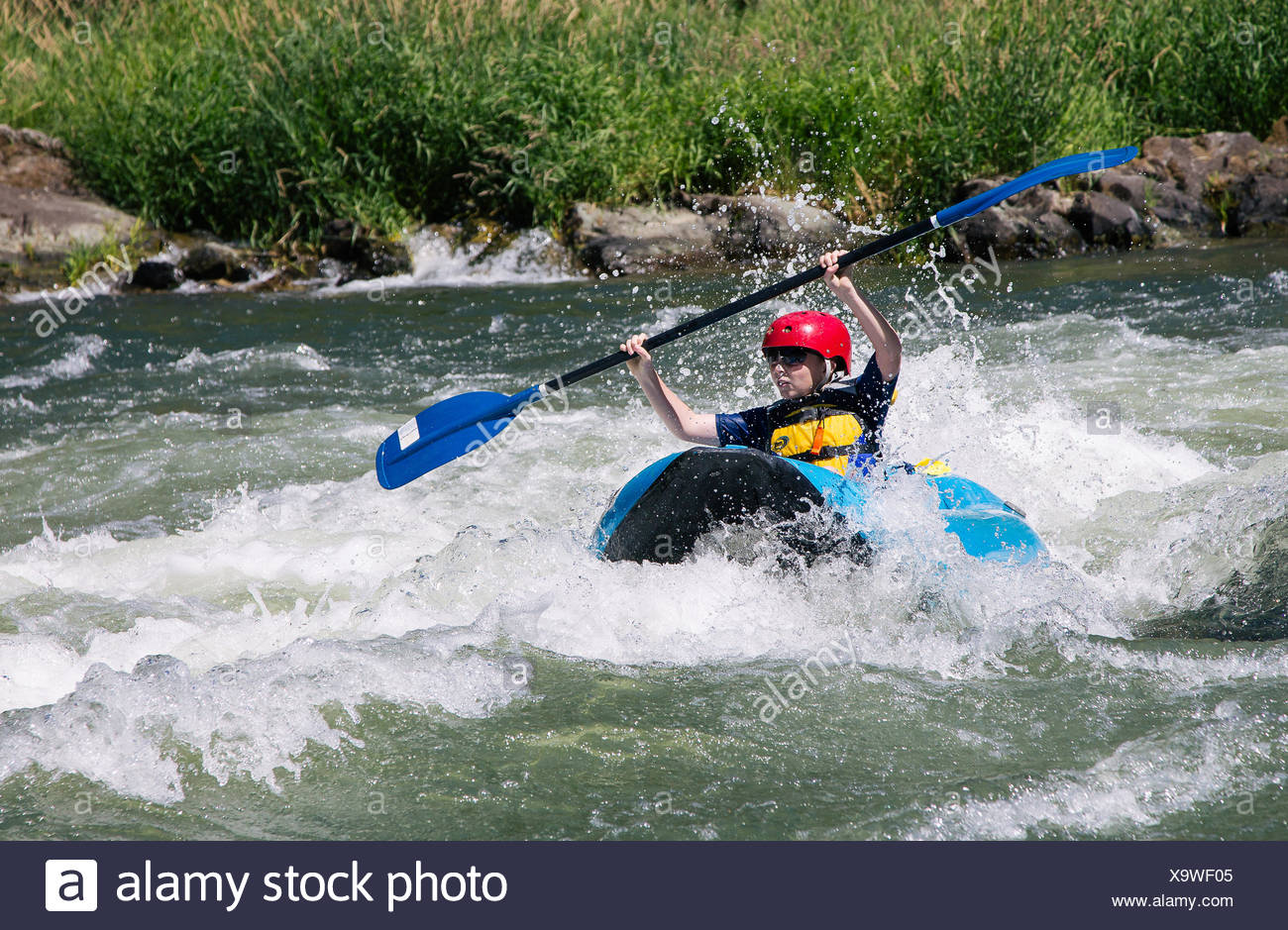 A boy paddles an inflatable kayak through rapids on the Rogue River. - Stock Image