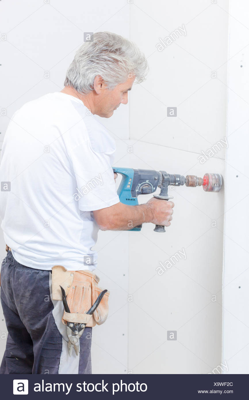 Builder using drill with attachment - Stock Image