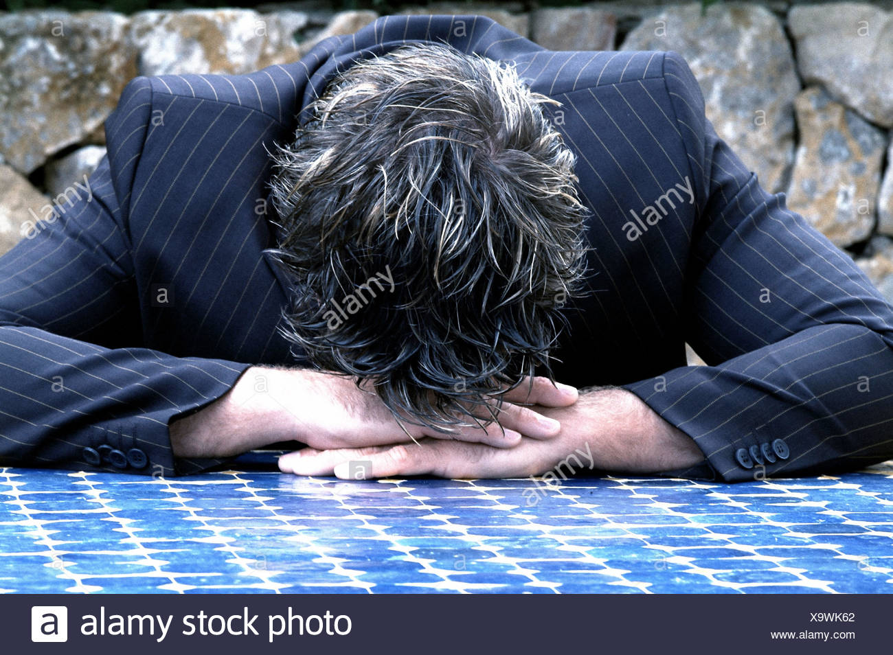 Man, suit, mosaic table plate,  Rested head, knocked down,  depress Emotion, businessman, failure, problem, worries, disappointment, mourning, resignation, descouple, losers, failures, failure, business, tiredness, exhaustion, negative - Stock Image