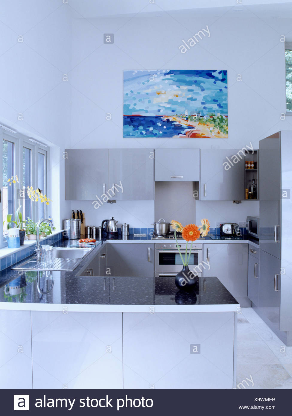 Granite Topped Worktops In Modern White Kitchen With Pale Grey Fitted Wall Units And Large Coastal Picture Stock Photo Alamy