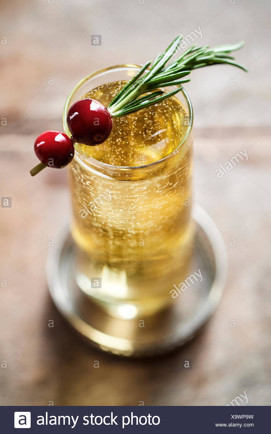 Beautiful champagne drink bubbling in stemless flute with a rosemary and cranberry garnish. - Stock Image