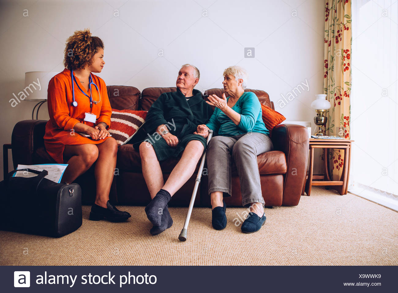 Elderly Couple with Home Carer - Stock Image