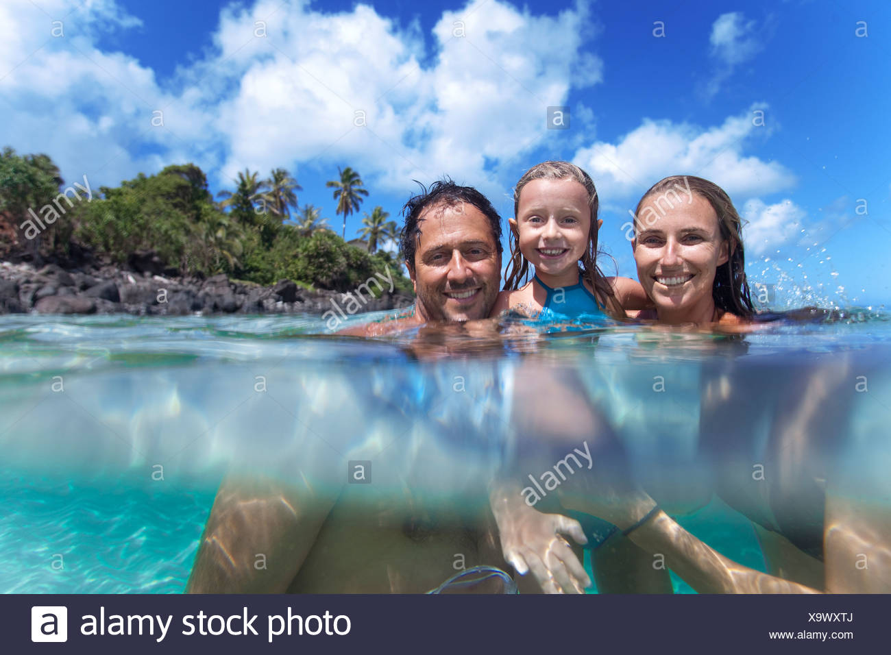 A split level view of a young family in the water at waimea Bay. - Stock Image