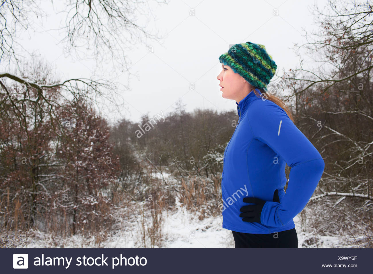 Female runner taking a break in winter scene - Stock Image