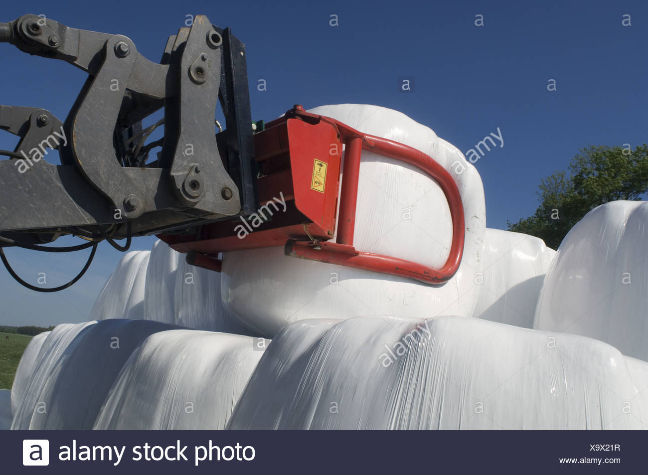 Plastic wrapped round silage bales, stacked onto pile with mechanical loader, Sweden - Stock Image