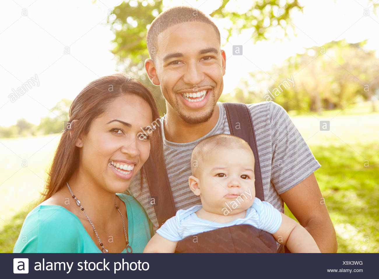Family With Baby Son In Carrier Walking Through Park - Stock Image